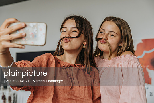 Friends making fake mustache with hair while taking selfie at home - p300m2214071 by Mareen Fischinger