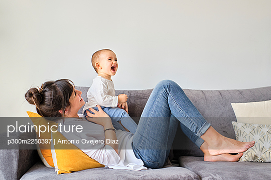 Mother playing with baby daughter on sofa - p300m2250397 by Antonio Ovejero Diaz