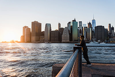 USA, Brooklyn, woman leaning on railing looking at view in the evening - p300m1205215 by Uwe Umstätter