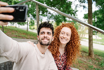 Smiling young couple taking selfie through mobile phone in public park - p300m2287585 by COROIMAGE