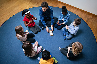 High angle view of teacher playing with children on floor at school - p426m1179425 by Maskot