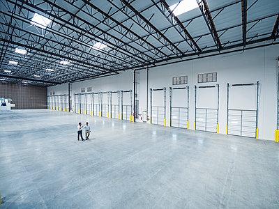 Businessmen walking near loading docks in empty warehouse - p555m1305149 by Erik Isakson