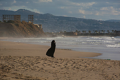 Muslim woman wearing burqa standing on the beach  - p794m1510976 by Mohamad Itani