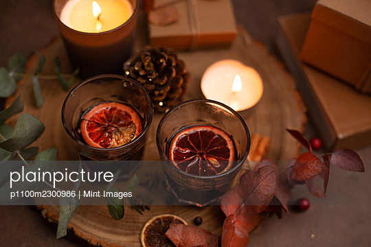 Christmas, wine glasses of mulled wine, lit candles and table decorations - p1100m2300986 by Mint Images