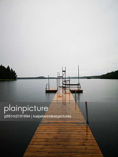 Bathing lake with wooden pier in the rain - p551m2191694 by kaipeterstakespictures