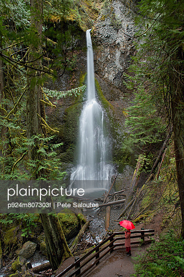Woman with umbrella admiring waterfall - p924m807303f by Pete Saloutos
