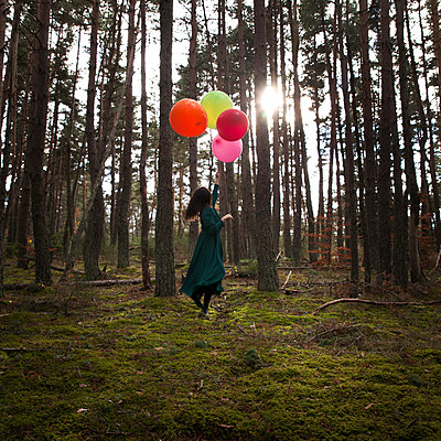 Woman with balloons in the forest - p1105m2134541 by Virginie Plauchut