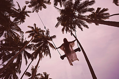 Young woman on a swing among palm trees - p1108m1194385 by trubavin
