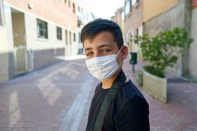 Boy with beautiful green eyes wearing a mask on the street - p1166m2201187 by Cavan Images