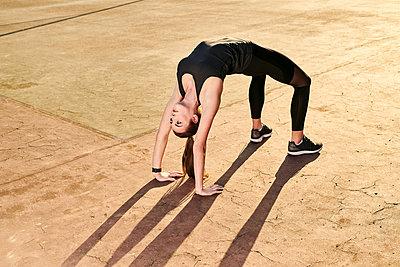 Sportive woman doing yoga, bridge position - p300m2004616 by Markus Mielek
