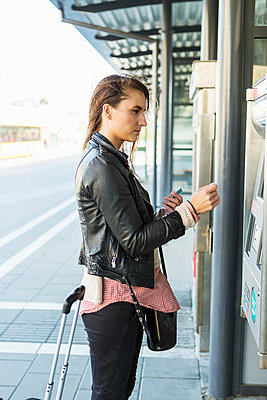 Side view of businesswoman buying ticket at railway station - p426m1085550f by Kentaroo Tryman