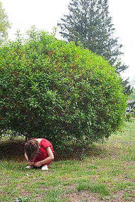 A Little Girl Hiding By Bush - p463m1064530 by Yo Oura
