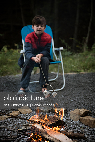 Young boy roasting marshmallows on a metal stick over a fire. - p1166m2214650 by Cavan Images