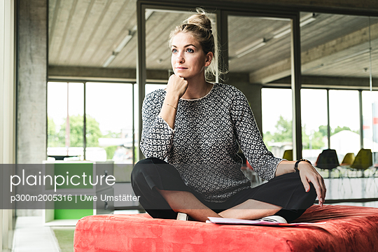 young businesswoman working in modern office, sitting on stool, thinking - p300m2005316 von Uwe Umstätter