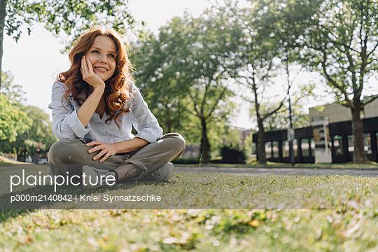 Smiling redheaded woman sitting on grass verge - p300m2140842 by Kniel Synnatzschke