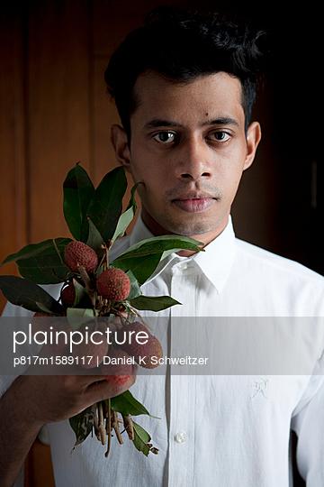 Inder hält frische Litschi Früchte - p817m1589117 von Daniel K Schweitzer