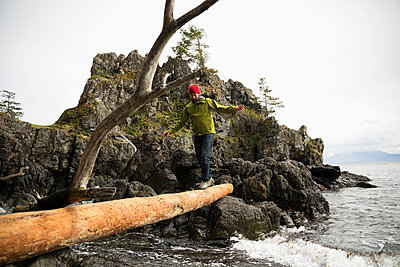 Male backpacker crossing fallen log over ocean - p1192m2000412 by Hero Images