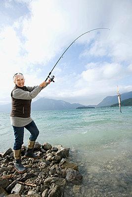 Germany, Bavaria, Walchsensee, Senior woman fishing in lake - p3007280f by Westend61