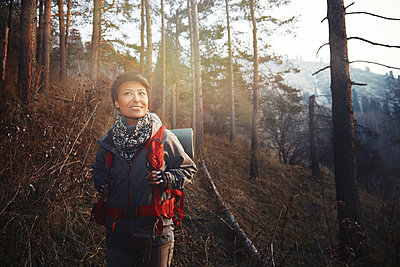 Mid adult woman smiling while hiking in forest - p300m2281492 by Arman Zhenikeyev