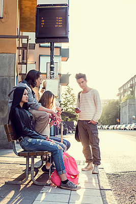 High school students waiting at bus stop - p426m958673f by Maskot