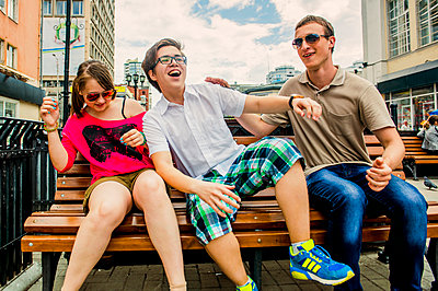 Caucasian friends playing on city bench - p555m1411601 by Aleksander Rubtsov