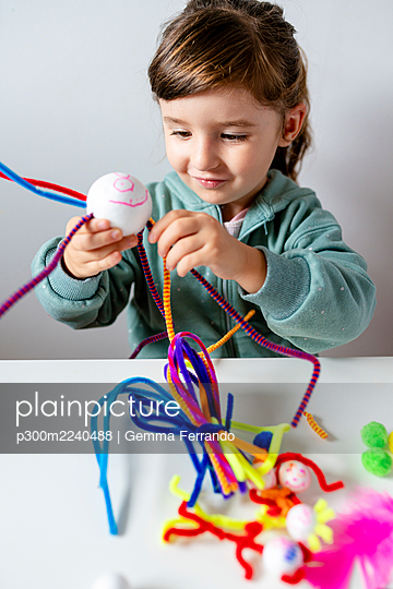 Smiling girl making toys of styrofoam ball and pipe cleaners while sitting at home - p300m2240488 by Gemma Ferrando