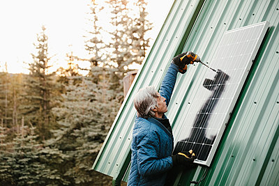 Man installing solar panel on cabin roof - p1192m2094304 by Hero Images