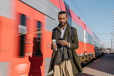 Portrait of stylish man using smartphone next to a train - p300m2154613 by Hernandez and Sorokina