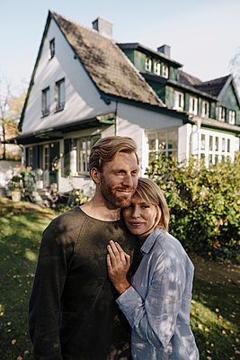 Smiling couple standing in front of their home - p300m2167228 by Kniel Synnatzschke