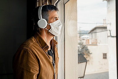 Man wearing protective mask and white headphones looking out of the window - p300m2189083 by Rafa Cortés