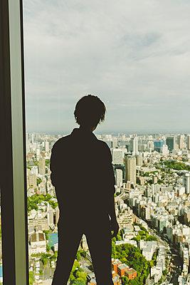 Frau steht blickt auf die Hochhäuser von Tokio - p432m2093397 von mia takahara