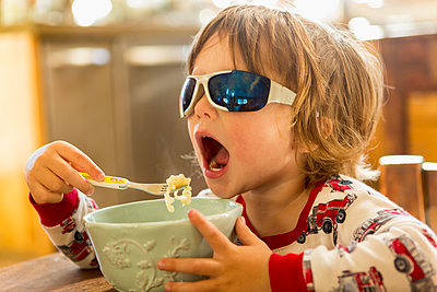 Caucasian boy in sunglasses eating in kitchen - p555m1311596 by Marc Romanelli