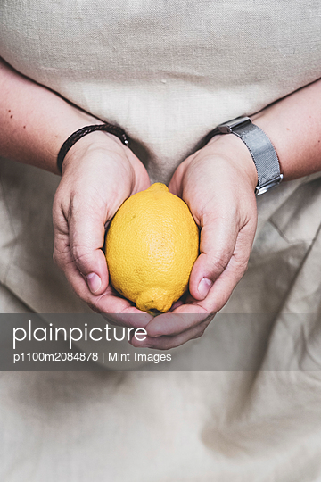 Close up of person holding fresh lemon. - p1100m2084878 by Mint Images