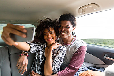 Happy couple taking selfie while traveling in car - p1166m1577581 by Cavan Images