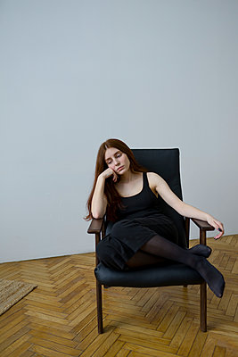Young woman with brown hair sitting in armchair - p1646m2237669 by Slava Chistyakov