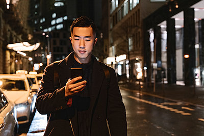 Man using smartphone while walking in the city at night - p300m2188081 by Hernandez and Sorokina