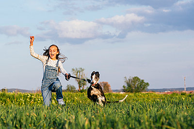 Cheerful girl running with dog on agricultural field - p300m2282025 by Jose Luis CARRASCOSA