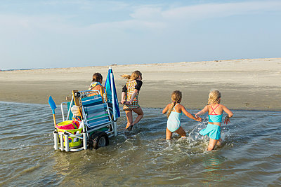 Caucasian boy and girls pulling cart on beach - p555m1522782 by Marc Romanelli