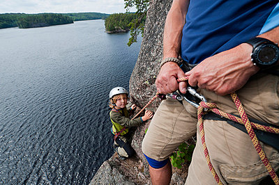 Father and son climbing together over lake - p575m696328f by Fredrik Schlyter