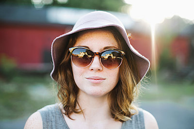 Woman wearing sunglasses and sun hat looking at camera - p924m1157670 by Lena Mirisola