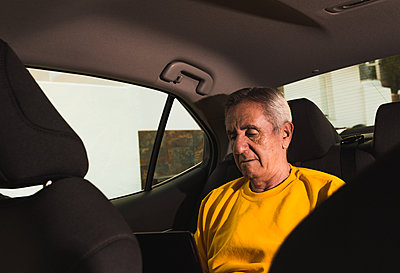 An elderly man using a laptop in the back seat of the car - p1166m2212938 by Cavan Images