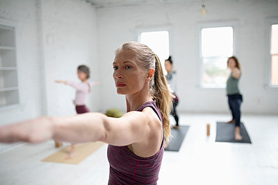 Focused woman practicing yoga warrior two pose in yoga class - p1192m1583342 by Hero Images