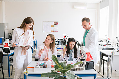 Students and teacher in white coats discussing in science class - p300m2250194 by Hernandez and Sorokina