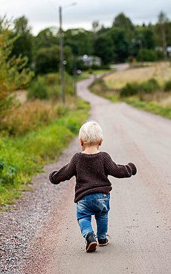 Finland, Uusimaa, Raasepori, Karjaa, Baby boy (12-17 months) walking country road - p352m1100947f by Nina Ahtola