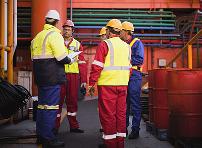 Workers talking on oil rig - p42915042f by Hybrid Images