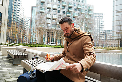 UK, London, Man reading newspaper on bench - p924m2271226 by Peter Muller