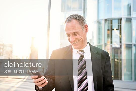 Geschäftsmann mit Smartphone - p890m1217291 von Mielek