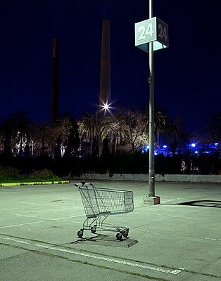 Shopping trolley abandoned in a car park outside a shopping mall at night in Barcelona (II) - p1072m829073 by Joan Seculi