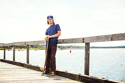 Portrait of man with longboard standing on pier against clear sky - p1166m985486f by Cavan Images