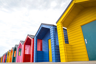 Line of brightly coloured beach huts - p1302m1573491 by Richard Nixon